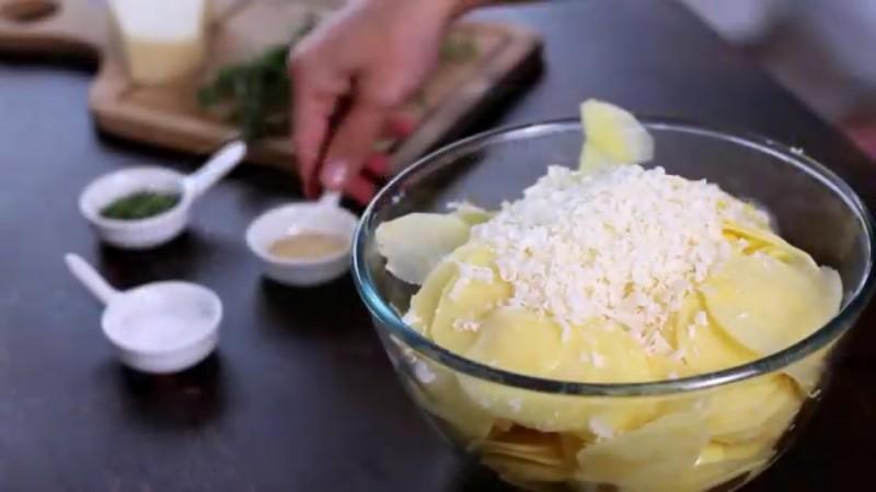 Trzemy ser i posypujemy nim pokrojone ziemniaki. Doprawiamy solą, pieprzem,...